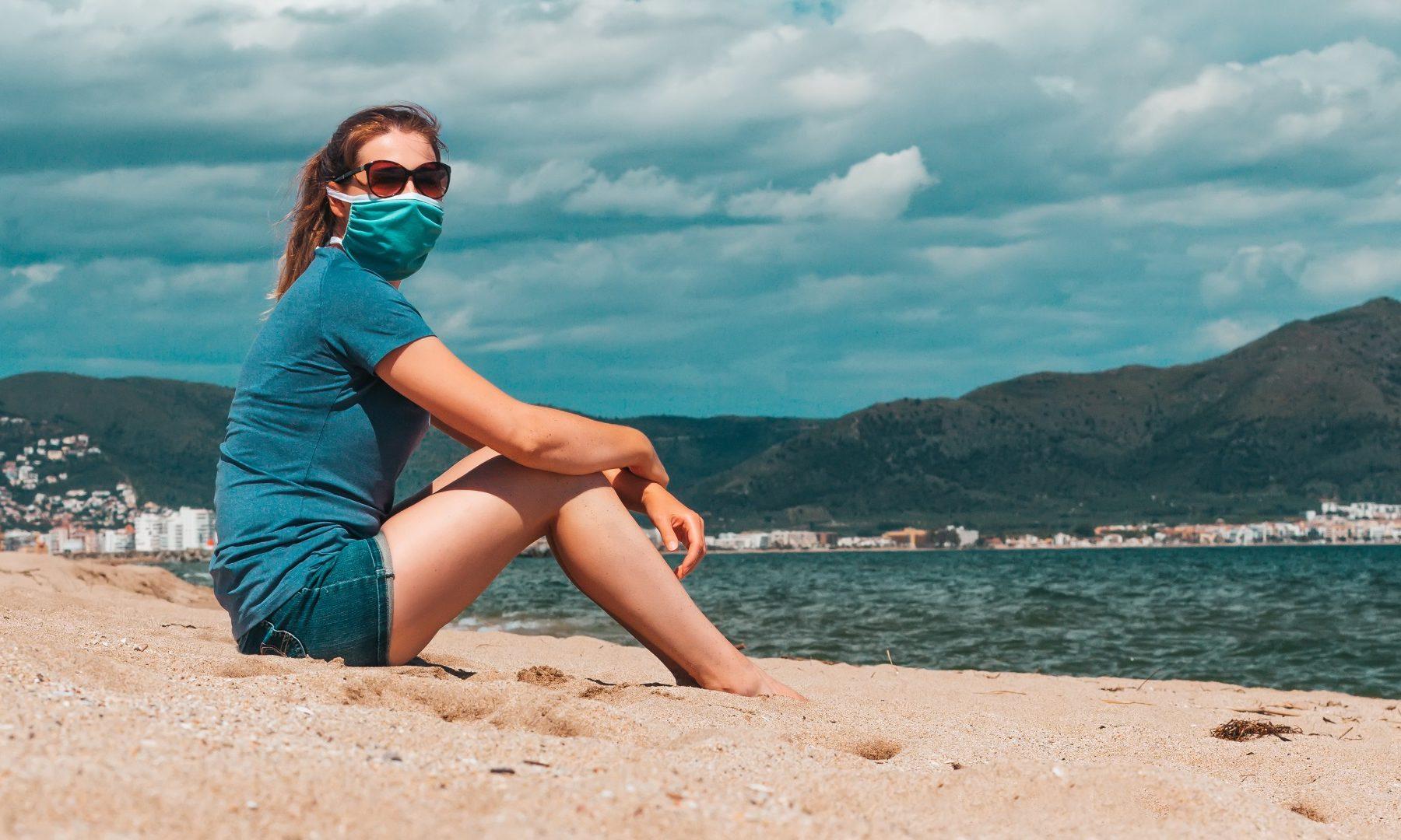 Frau mit Maske am Strand